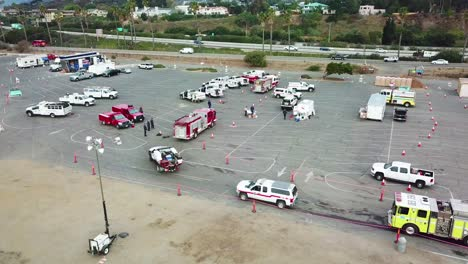 High-angle-pan-of-firefighters-in-fire-trucks-lining-up-for-duty-at-a-staging-area-during-the-Thomas-Fire-in-Ventura-California-in-2017