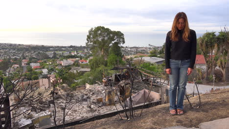 A-woman-stands-in-front-of-a-burned-home-after-the-Thomas-fire-in-Ventura-California