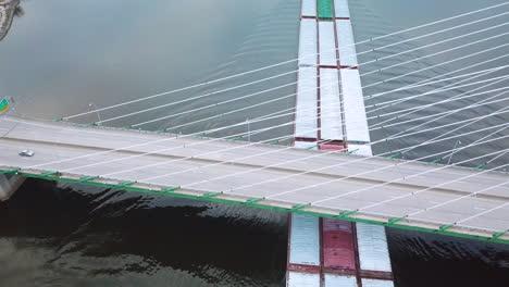 Antena-De-Una-Barcaza-De-Carbón-Empujada-Por-Un-Remolcador-Subiendo-El-Río-Mississippi-Cerca-De-Burlington-Iowa-Con-Puente-Colgante-En-Primer-Plano