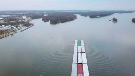Antena-De-Una-Barcaza-De-Carbón-Empujada-Por-Un-Remolcador-Subiendo-Por-El-Río-Mississippi-Cerca-De-Burlington-Iowa-Con-Puente-Colgante-En-Primer-Plano-1