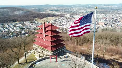 Aerial-over-Reading-Pennsylvania-Asian-temple-and-American-flag-with-city-background-1
