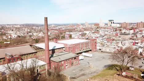 Aerial-over-an-abandoned-American-factory-with-smokestack-near-Reading-Pennsylvania-1