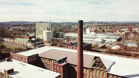 Aerial-over-an-abandoned-American-factory-with-smokestack-near-Reading-Pennsylvania-3