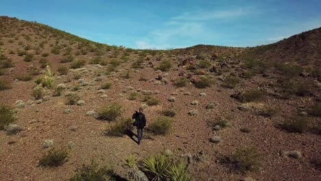 Drone-aerial-of-a-photographer-walking-with-and-tripod-across-a-desert-with-long-shadows