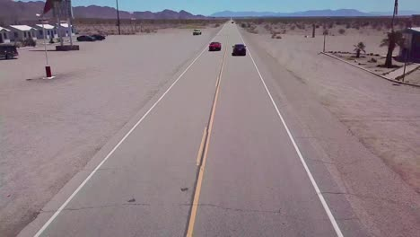 Drone-aerial-over-a-lonely-desert-highway-in-Arizona-with-Route-66-painted-on-the-pavement-and-car-passing-underneath-2
