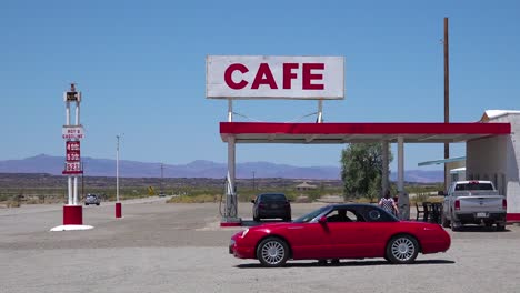 Establishing-shot-of-a-lonely-desert-gas-station-and-hotel-motel-cafe-in-the-Mojave-Desert-with-Thunderbird-car-in-forground