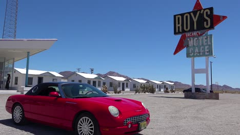 Establishing-shot-of-a-lonely-desert-gas-station-and-hotel-motel-cafe-in-the-Mojave-Desert-with-Thunderbird-car-in-forground-1