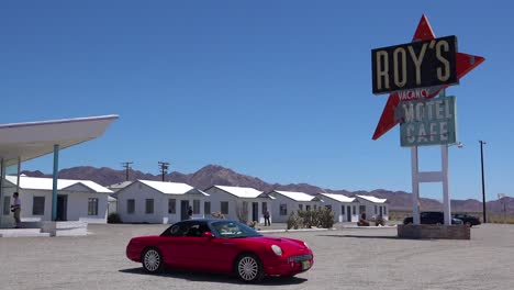 Establishing-shot-of-a-lonely-desert-gas-station-and-hotel-motel-cafe-in-the-Mojave-Desert-with-Thunderbird-car-in-forground-2