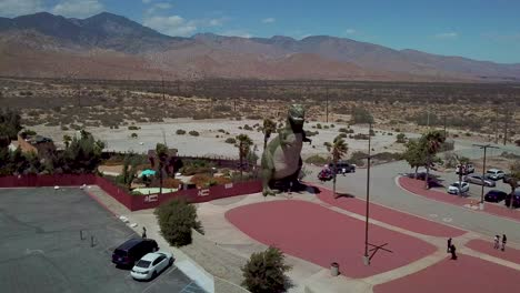 Aerial-over-a-giant-artifical-dinosaur-looming-over-visitors-as-a-roadside-attraction-in-the-Mojave-Desert-near-Cabazon-California