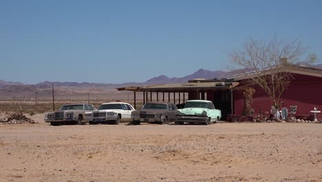 Old-classic-Cadillac-cars-and-other-vintage-automobiles-sit-outside-a-remote-ranch-house-in-the-Mojave-Desert