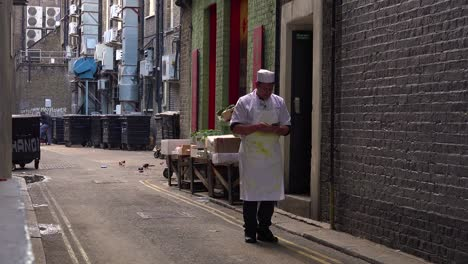 A-chef-checks-his-email-on-his-phone-while-standing-in-an-alley-outside-a-restaurant