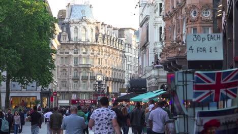 Mucho-Tráfico-Peatonal-Y-Peatones-Se-Mueven-A-Través-De-Leicester-Square-Londres-Inglaterra