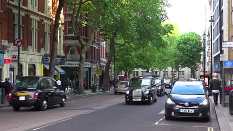 Traditional-London-taxi-cabs-head-down-a-street-in-a-downtown-neighborhood