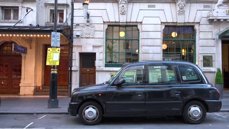 A-London-taxi-cab-is-parked-outside-a-restaurant-or-pub