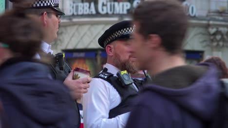 Dos-Policías-Bobby-De-Londres-Beben-Café-Y-Observan-A-Los-Peatones-En-Un-Concurrido-Distrito-Turístico