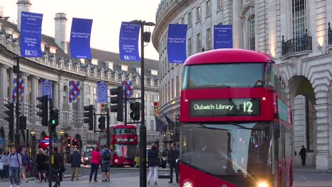 Early-evening-doubledecker-bus-and-London-taxi-traffic-moves-through-Piccadilly-Circus