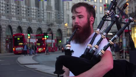 A-Scottish-bagpiper-performs-on-the-street-near-London\-s-Piccadilly-Square