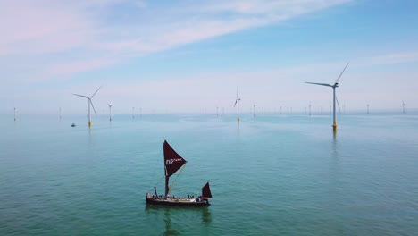 A-flat-bottomed-sailing-barge-sailboat-moves-up-the-Thames-River-Estuary-in-England-amidst-numerous-wind-turbine-windmills