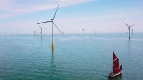 A-flat-bottomed-sailing-barge-sailboat-moves-up-the-Thames-River-Estuary-in-England-amidst-numerous-wind-turbine-windmills-1