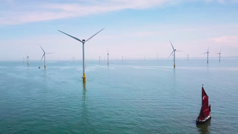 A-flat-bottomed-sailing-barge-sailboat-moves-up-the-Thames-River-Estuary-in-England-amidst-numerous-wind-turbine-windmills-2
