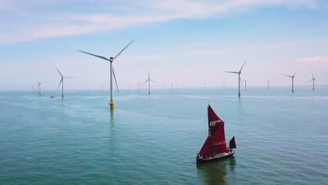 A-flat-bottomed-sailing-barge-sailboat-moves-up-the-Thames-River-Estuary-in-England-amidst-numerous-wind-turbine-windmills-3