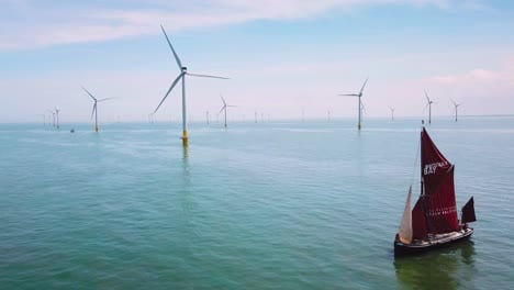 A-flat-bottomed-sailing-barge-sailboat-moves-up-the-Thames-Río-Estuary-in-England-amidst-numerous-wind-turbine-windmills-4