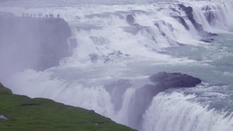 The-spectacular-and-massive-waterfall-Gullfoss-flows-in-Iceland-with-tourists-on-cliff-in-distance