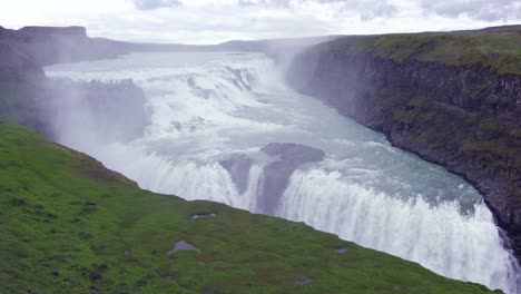 The-spectacular-and-massive-waterfall-Gullfoss-flows-in-Iceland-with-tourists-on-cliff-in-distance-1