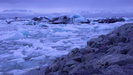 Pan-across-icebergs-sitting-in-a-glacial-bay-suggesting-global-warming-in-the-Arctic-at-Jokulsarlon-glacier-lagoon-Iceland-night