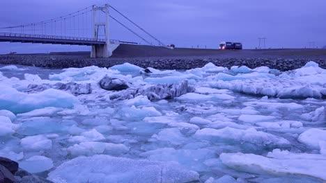 A-car-and-a-truck-cross-a-bridge-over-a-glacial-bay-in-the-Arctic-at-Jokulsarlon-glacier-lagoon-Iceland-night