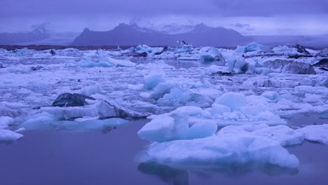 Pan-across-icebergs-sitting-in-a-glacial-bay-suggesting-global-warming-in-the-Arctic-at-Jokulsarlon-glacier-lagoon-Iceland-night-1