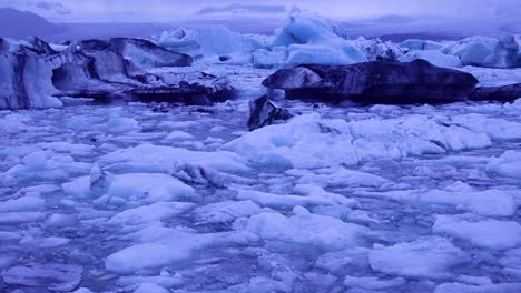 Tilt-up-to-icebergs-sitting-in-a-glacial-bay-suggesting-global-warming-in-the-Arctic-at-Jokulsarlon-glacier-lagoon-Iceland-night
