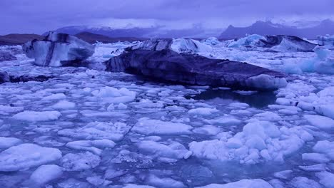 Slow-zoom-in-to-icebergs-sitting-in-a-glacial-bay-suggesting-global-warming-in-the-Arctic-at-Jokulsarlon-glacier-lagoon-Iceland-night