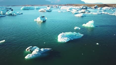 Drone-aerial-over-icebergs-moving-in-a-glacial-bay-Jokulsarlon-glacier-lagoon-Iceland-suggesting-global-warming