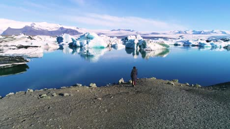 Aerial-of-a-woman-standing-along-the-shore-of-a-glacier-lagoon-in-the-Arctic-at-Jokulsarlon-glacier-lagoon-Iceland
