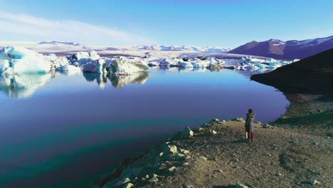Aerial-of-a-woman-standing-along-the-shore-of-a-glacier-lagoon-in-the-Arctic-at-Jokulsarlon-glacier-lagoon-Iceland-2