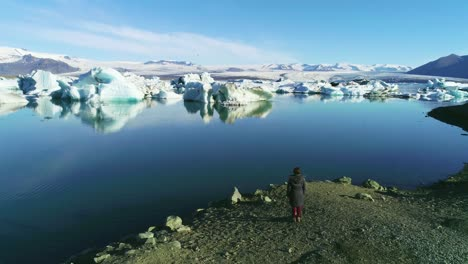 Aerial-of-a-woman-standing-along-the-shore-of-a-glacier-lagoon-in-the-Arctic-at-Jokulsarlon-glacier-lagoon-Iceland-3