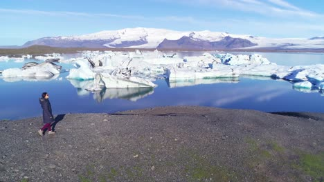 Aerial-of-a-woman-standing-along-the-shore-of-a-glacier-lagoon-in-the-Arctic-at-Jokulsarlon-glacier-lagoon-Iceland-5