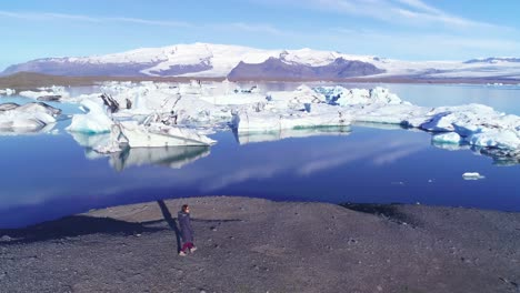 Aerial-of-a-woman-standing-along-the-shore-of-a-glacier-lagoon-in-the-Arctic-at-Jokulsarlon-glacier-lagoon-Iceland-6