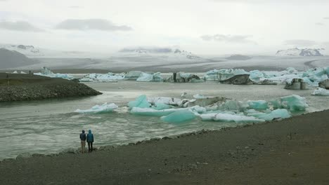 Two-people-stand-along-a-river-in-the-frozen-Arctic-Jokulsarlon-glacier-lagoon-in-Iceland-suggesting-global-warming