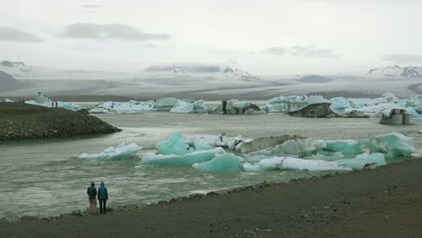 Two-people-stand-along-a-river-in-the-frozen-Arctic-Jokulsarlon-glacier-lagoon-in-Iceland-suggesting-global-warming-1