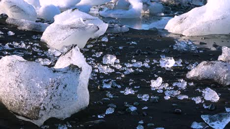 Icebergs-sit-on-black-sand-Diamond-Beach-Jokulsarlon-in-the-Arctic-Iceland-polished-and-glistening-like-jewels-3