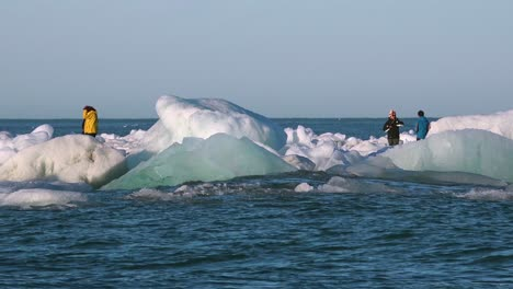 Tourists-walk-near-icebergs-drifting-in-the-Arctic-near-Jokulsarlon-Iceland