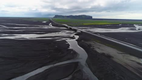 Aerial-along-a-road-and-bridge-over-a-large-dark-volcanic-flood-river-system-in-Iceland