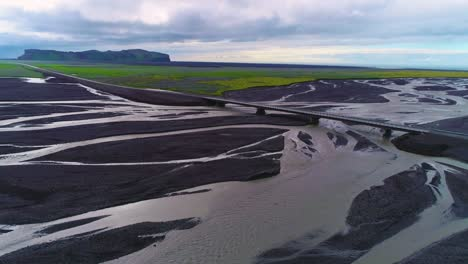 Aerial-of-a-car-along-a-road-and-bridge-over-a-large-dark-volcanic-flood-river-system-in-Iceland