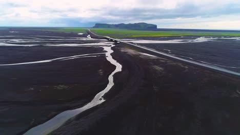Antena-De-Un-Coche-Circulando-Rápido-A-Lo-Largo-De-Una-Carretera-Y-Un-Puente-Sobre-Un-Gran-Sistema-Fluvial-De-Inundación-Volcánica-Oscura-En-Islandia
