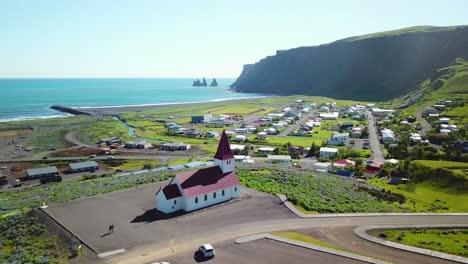 Toma-Aérea-De-Establecimiento-De-La-Ciudad-De-Vik-En-El-Sur-De-Islandia-Su-Icónica-Iglesia-