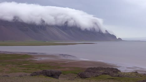 Establishing-shot-of-remarkable-beautiful-fjords-in-Iceland-with-clouds-and-fog-rolling-over-the-top