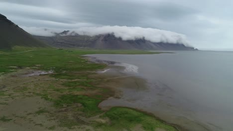 Stunning-aerial-shot-of-remarkable-beautiful-fjords-in-Iceland-with-clouds-and-fog-rolling-over-the-top