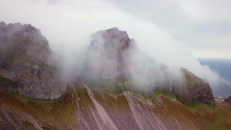 Toma-Aérea-De-Notables-Hermosos-Fiordos-En-Islandia-Con-Nubes-Y-Niebla-Rodando-Sobre-La-Parte-Superior